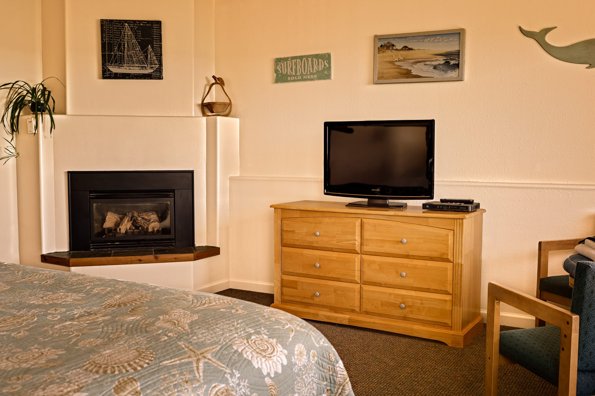 Bedroom with pillow top King size bed, fireplace, HDTV flatscreen, and dresser drawers in the extended stay Kitchen Suite hotel room at Inn of the Lost Coast Shelter Cove.