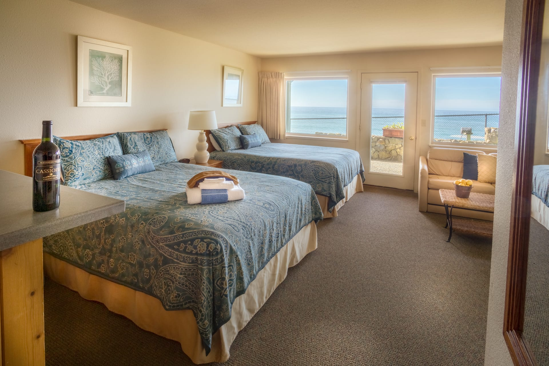 Double Queen Mini Suite oceanfront hotel room at Inn of the Lost Coast Shelter Cove with two Queen size beds, love seat sofa couch, coffee table, extended stay kitchenette, and patio with panoramic views of Shelter Cove rocky shorline.