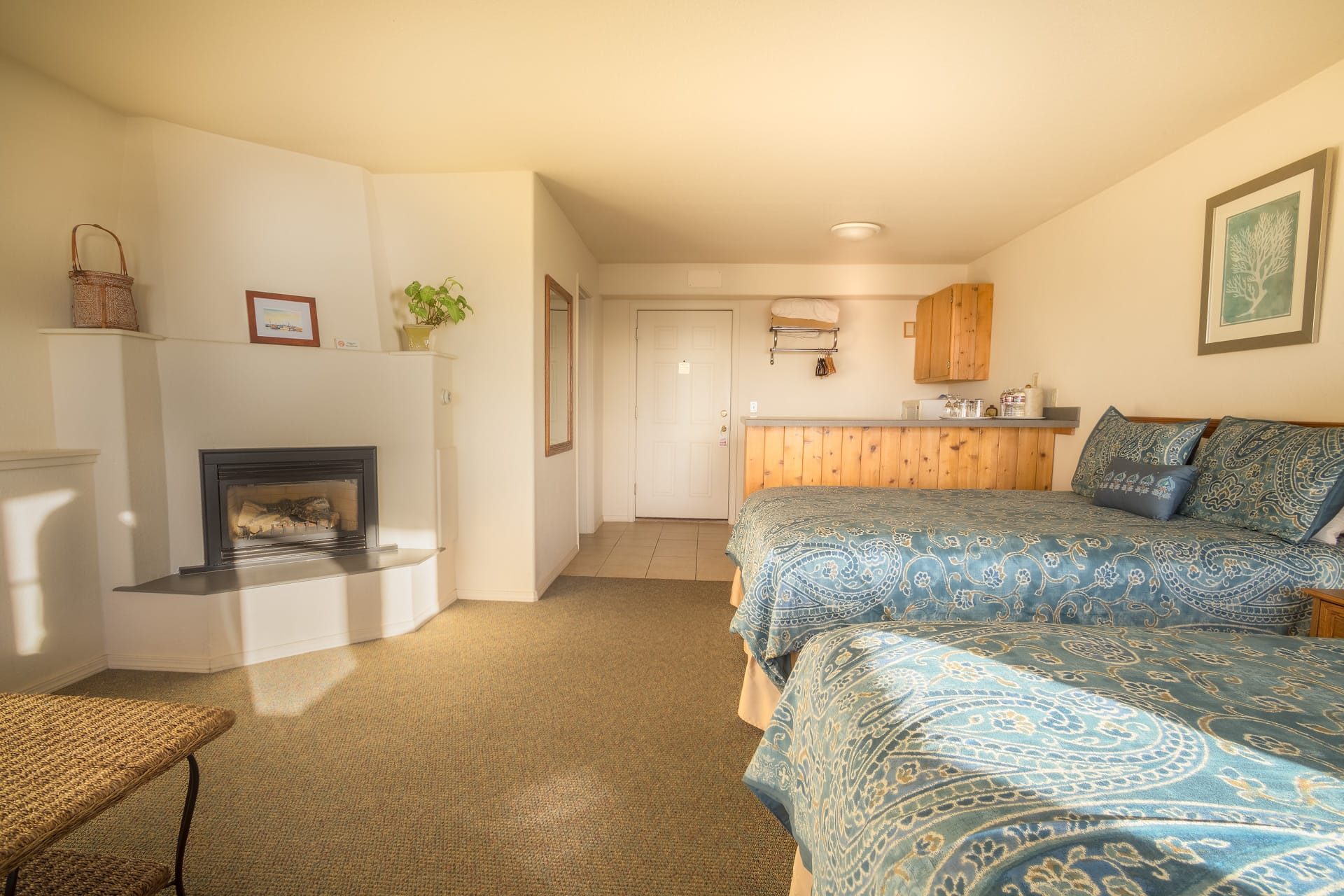Oceanfront Double Queen Mini Suite hotel room at Inn of the Lost Coast Shelter Cove with two Queen size beds, fireplace, and extended stay kitchenette with bar and bar stools.