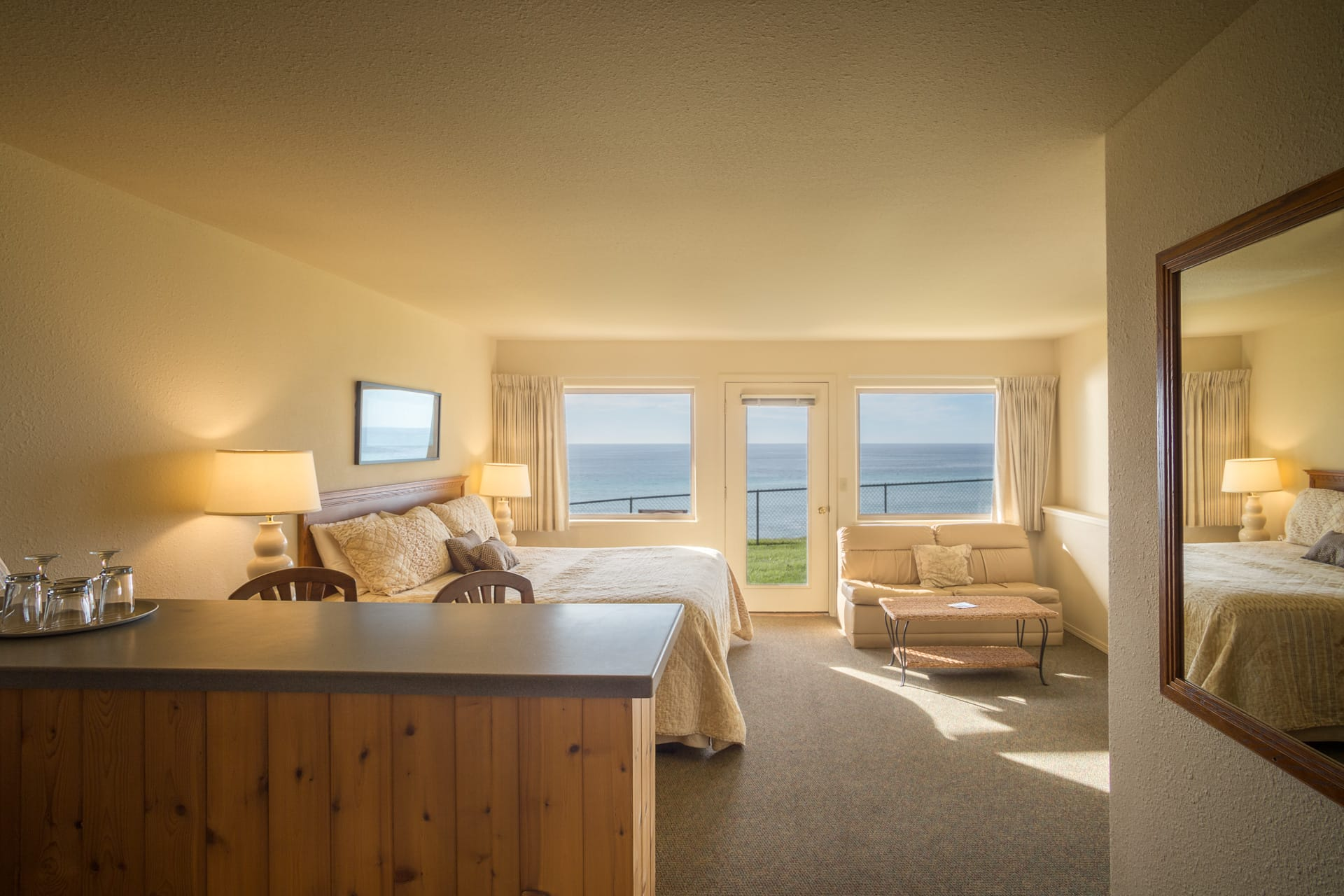 Inn of the Lost Coast Shelter Cove extended stay Mini Suite hotel room with whale watching ocean view, one King size bed, love seat sofa couch, whisk coffee table, and kitchenette with bar and bar stools.