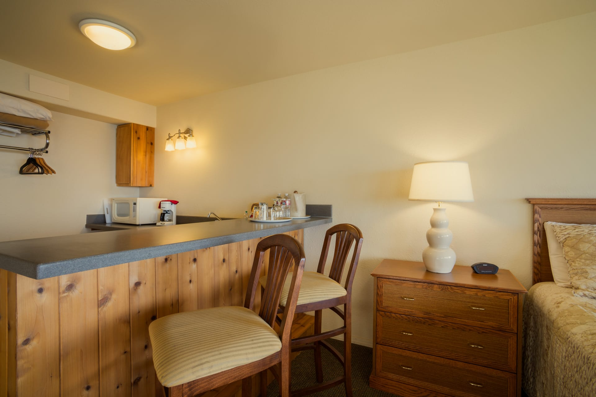 Kitchenette with bar and bar stools, microwave, mini refrigerator, sink, coffee maker, in this extended stay Mini Suite oceanfront hotel room at Inn of the Lost Coast Shelter Cove.