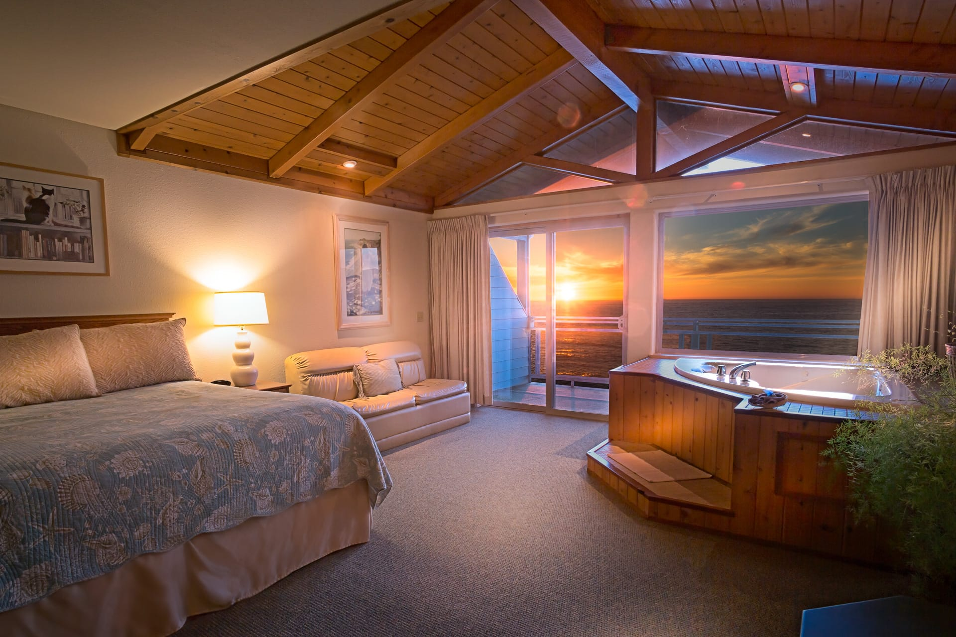 Luxury oceanfront Deluxe Spa Suite hotel room at Inn of the Lost Coast Shelter Cove. In-room hot tub positioned under exposed wood plank beam ceilings and flush against floor to ceiling windows provide an ocean sunset view from hot tub.