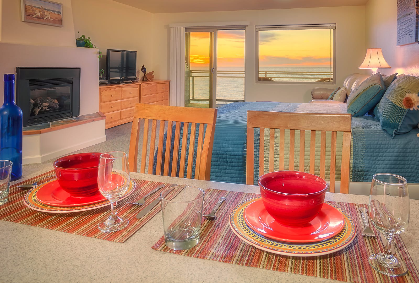 Meal setting on dining area of luxury Deluxe Kitchen Suite hotel room. King size bed, built-in fireplace with mantel, dresser drawers, flatscreen HDTV, and private balcony with panoramic view of Northern California Pacific Ocean sunset.