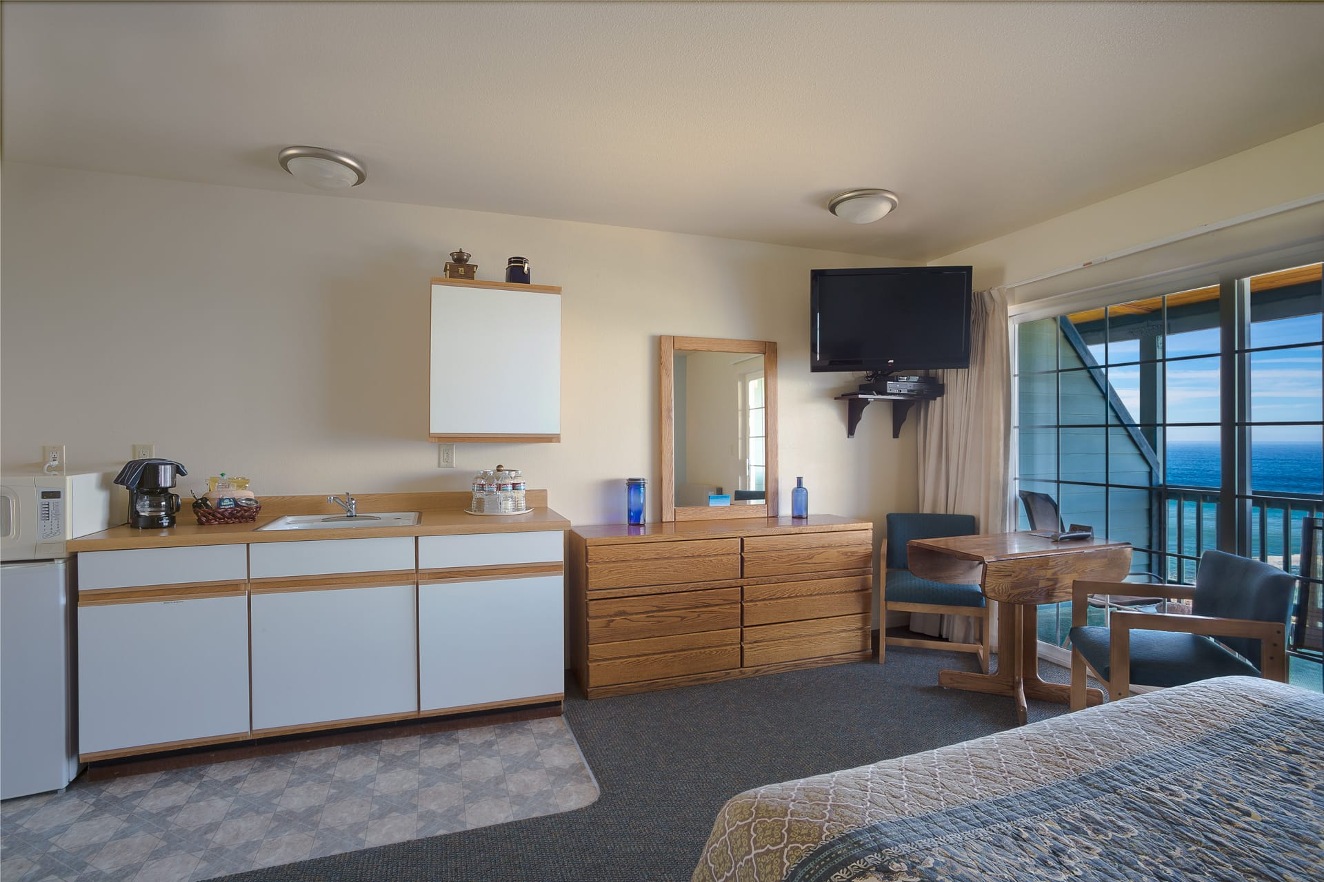 Inn of the Lost Coast Standard Double Queen Guestroom extended stay kitchenette with microwave, mini refrigerator, dresser drawers, HD flatscreen with Direct TV, workspace, and balcony view of the Northern California Pacific Ocean.
