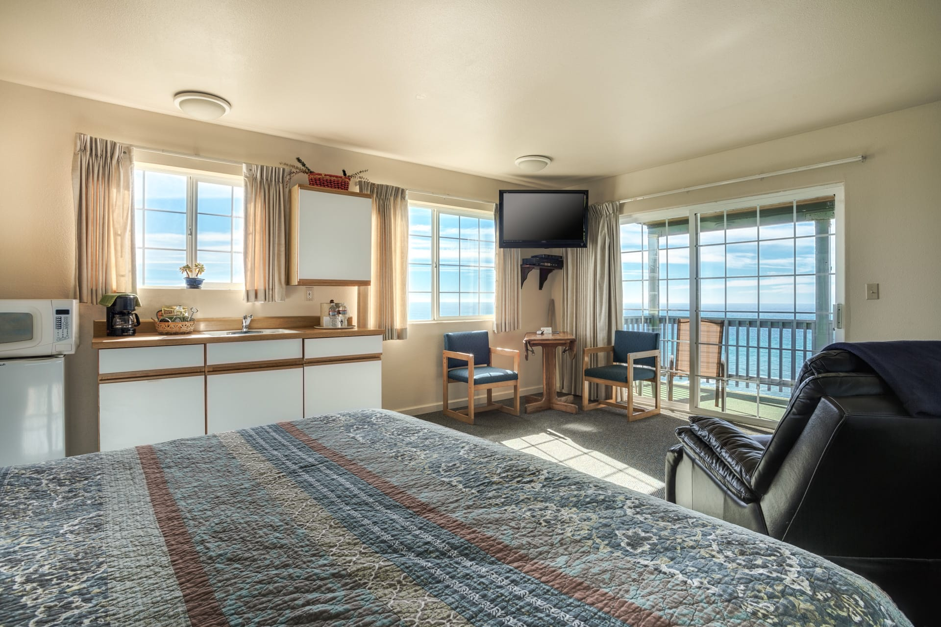 Inn of the Lost Coast oceanfront Corner Guestroom featuring extended stay kitchenette with microwave, mini refrigerator, food prep countertops, sink, and plenty of cabinets for food storage. Windows over kitchenette sink and workspace area flood this guestroom with sunlight and provide panoramic views of Shelter Cove from both inside guestroom as well as on private balcony.
