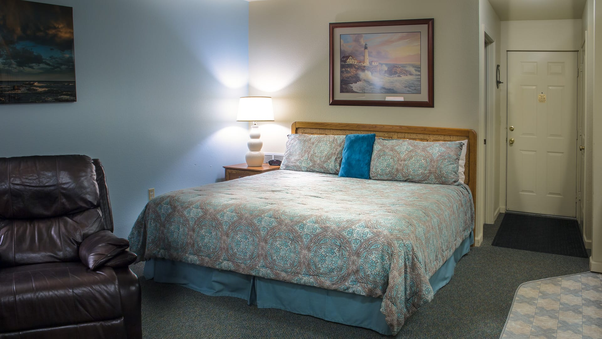 Standard Hotel Guestroom at Inn of the Lost Coast Shelter Cove with King size bed, leather reclining chair, and original artwork.
