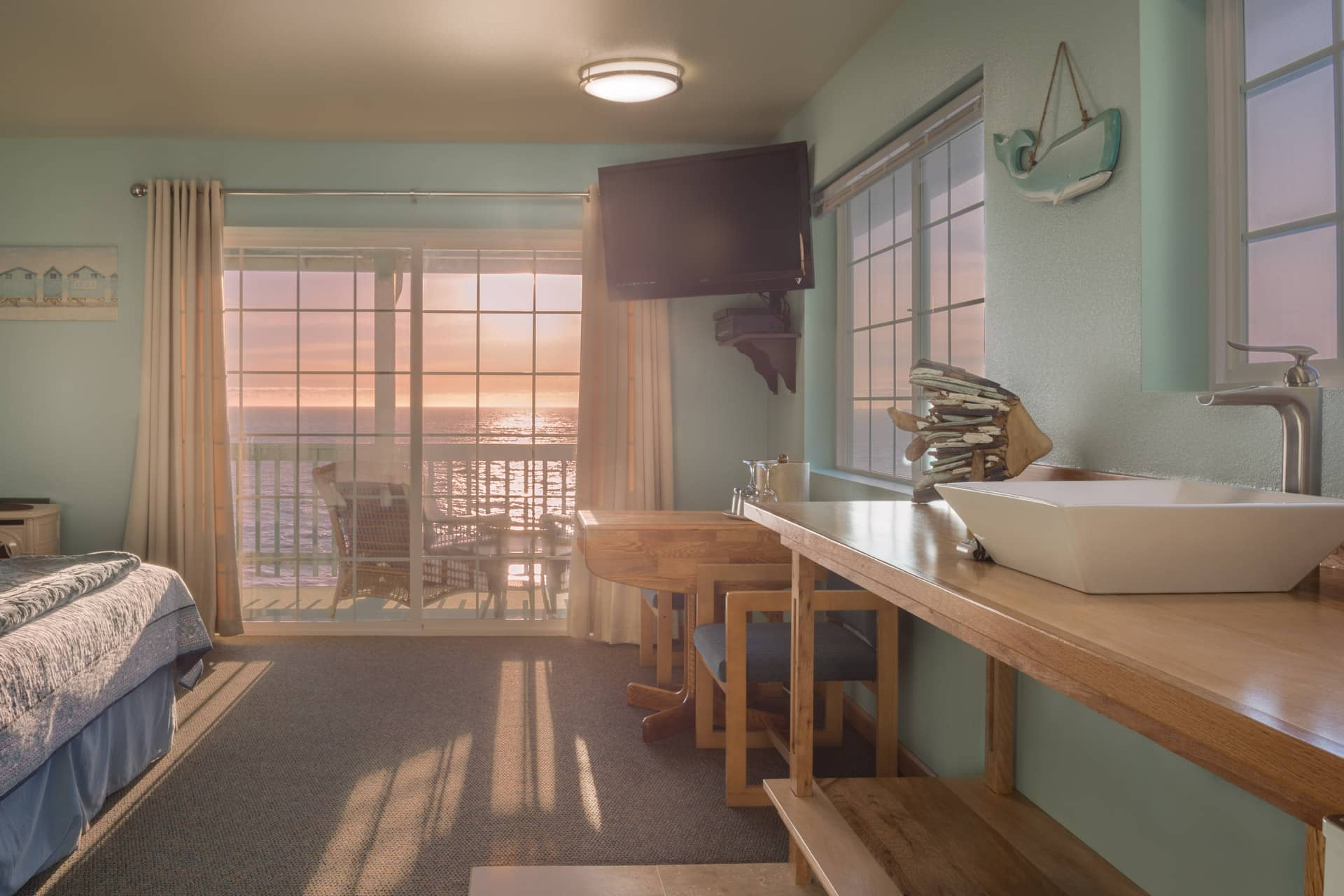 Sunset view at the oceanfront Inn of the Lost Coast Shelter Cove, from within the Deluxe Corner Guestroom hotel room with kitchenette, sink, and private balcony overlooking the Shelter Cove coastal bluffs.