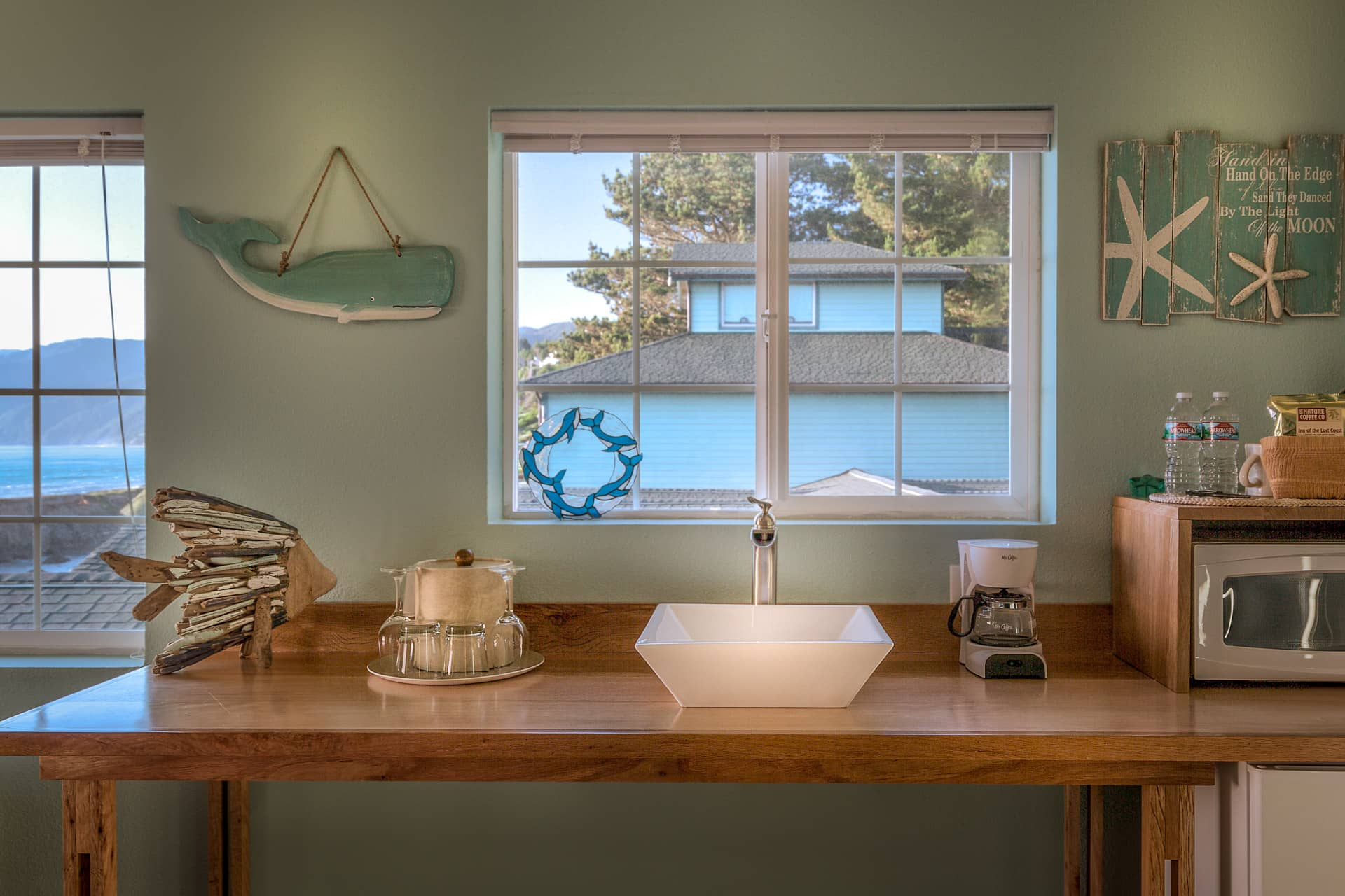 Custom wood kitchenette with sink, coffee maker, microwave, wine and water glasses, underneath window with norther view of Shelter Cove coastline, in the Deluxe Corner Guestroom at the oceanfront Inn of the Lost Coast Shelter Cove.