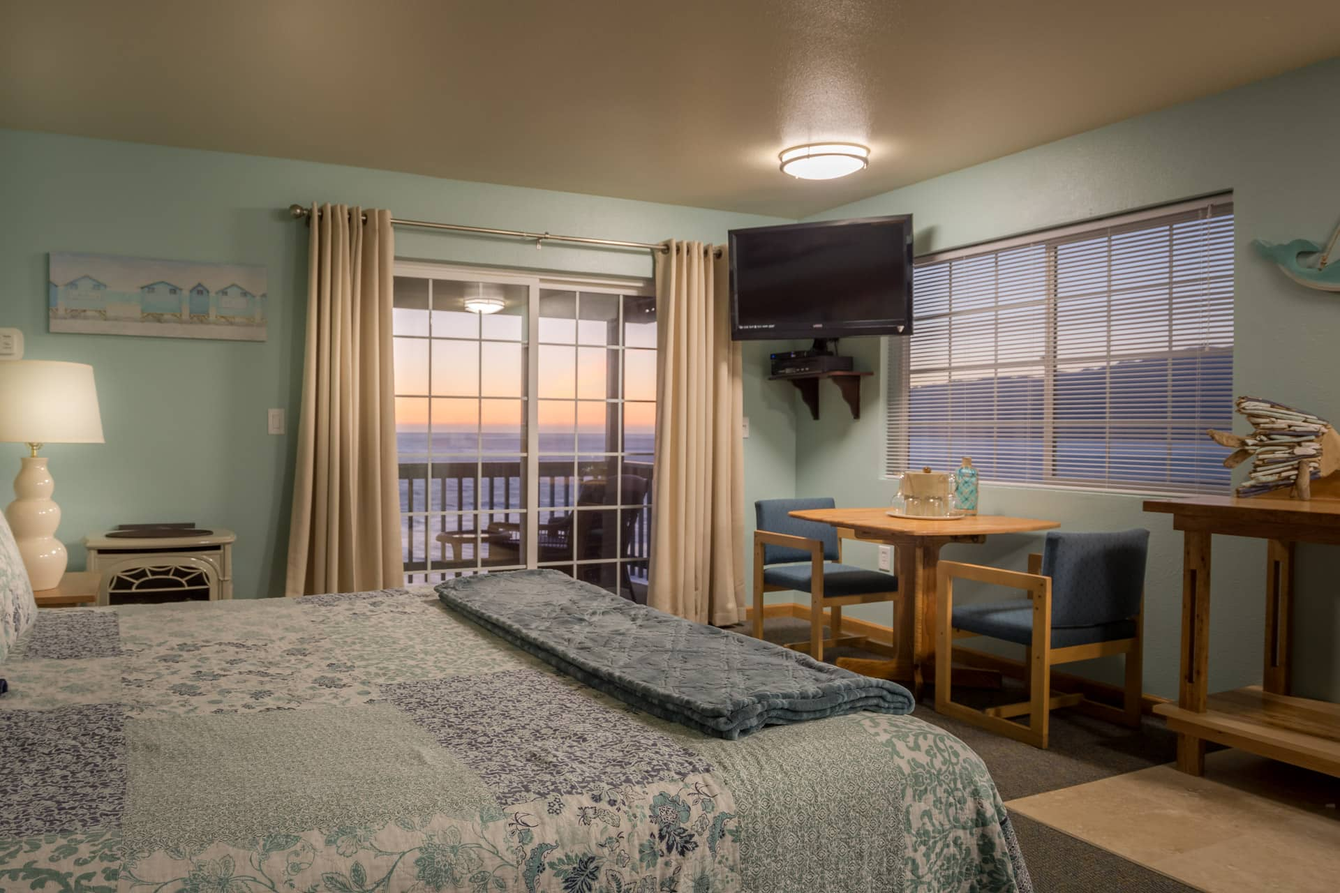 Deluxe Corner Guestroom hotel room at the oceanfront Inn of the Lost Coast Shelter Cove with King size bed, HDTV flatscreen, dining area, and furnished private balcony at sunset with ocean view of Shelter Cove coastline.