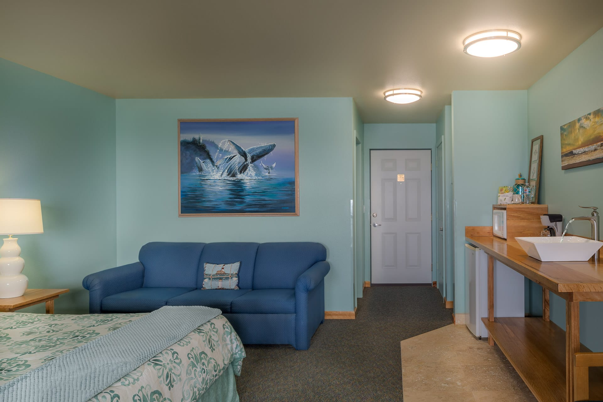Spacious Deluxe Guestroom hotel room at the oceanfront Inn of the Lost Coast with King size bed, kitchenette, mini refrigerator, microwave, sofa couch, and original artwork.